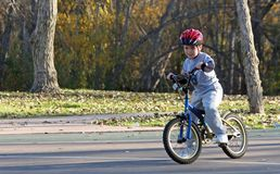 Boy riding bicycle at park #2. A six year old boy rides his bicycle at a park on a sunny afternoon. He is wearing a safety helmet and a gray sweatsuit Royalty Free Stock Image