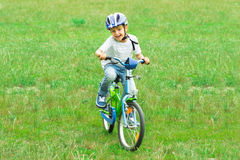 Boy Riding Bicycle. Photo Of Happy Boy Riding Bicycle In Park Royalty Free Stock Photography