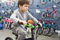 Boy riding bicycle in sport shop Stock Photography