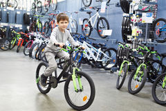 Boy riding bicycle in sports supermarket Stock Photo