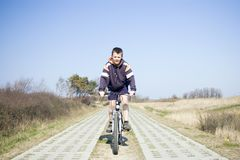 Boy riding a bike. Central composition, a boy riding a bike, in the middle of a path consisting of two concrete slabs lines. Clear blue sky Stock Photography