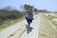 Boy riding a bike. Central composition, a boy riding a bike, in the middle of a path consisting of two concrete slabs lines. Clear blue sky Stock Image