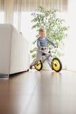Boy riding bike indoors. Smiling boy riding bike at home Stock Image