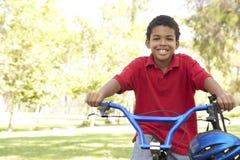 Boy Riding Bike In Park. African American Boy Riding Bike In Park Smiling royalty free stock photo