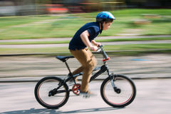 Boy riding a bike in a park Stock Images