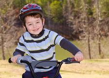 Boy riding bike with safety helmet. Outdoors at park Royalty Free Stock Image