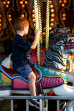 Boy Riding on Carousel. Young boy riding on white carousel horse Stock Photo