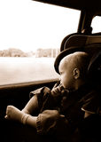 Boy riding in carseat. Young boy, riding bucked in a carseat looking out the window thoughtfully.  Peaceful subtle sepia photo of a small child during a car ride Royalty Free Stock Images