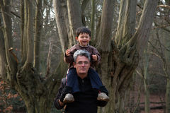 Boy riding on dad's shoulders Stock Image