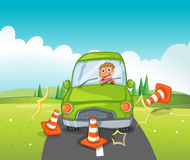 A boy riding on a green car bumping the traffic cones Royalty Free Stock Photography