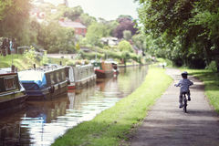 Boy riding his bike. Riding a bicycle on a tow path by a canal concept for healthy lifestyle, exercising and vacations royalty free stock photo