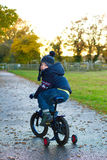 Boy riding his bike through a countryside path Stock Images