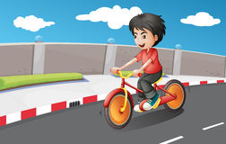 A boy riding in his bike with orange wheels Stock Photos