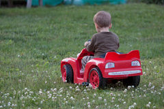 Boy riding his car. Young boy riding his toy car in the grass Royalty Free Stock Photography