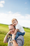 Boy riding his father's shoulders. In a field royalty free stock photo
