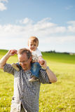 Boy riding his father's shoulders. In a field stock images