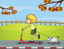 A boy riding with his scooter followed by his pet Royalty Free Stock Images