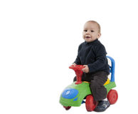 Boy riding his toy car. Little boy riding his multicolored toy car on a white background royalty free stock photo