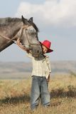 Boy riding a horse on farm outdoors Stock Images