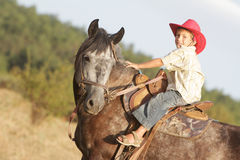 Boy riding a horse on farm outdoors Royalty Free Stock Images