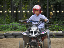 Boy riding on kids' quadricycle, having fun. Boy rives a small motorbike and has a lot of fun Stock Photo