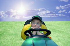 BOY ON A RIDING MOWER RESTING. A young boy sitting on a riding mower outside in the field on a sunny summer day blue sky and clouds Royalty Free Stock Images