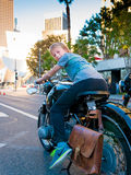 Boy Riding Parked Vintage Motorcycle in Downtown Los Angeles Stock Photo