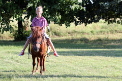 Boy riding pony horse Stock Photos