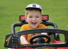 Boy riding racing car. Happy young preschool boy with baseball cap riding on toy racing car or go-kart; green grass background Royalty Free Stock Images