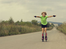 Boy riding on rollers on the road Royalty Free Stock Photo