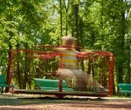 Boy riding roundabout playground Royalty Free Stock Photo