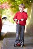 Boy Riding Scooter On His Way To School Stock Images