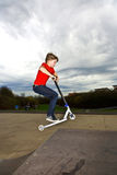 Boy riding a scooter is jumping at Stock Photos