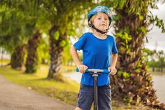 Boy riding scooters, outdoor in the park, summertime. Kids are happy playing outdoors.  royalty free stock photography