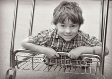 Boy Riding on Shopping Cart. A black and white portrait of a young boy riding on the bottom of a shopping cart in a plaid shirt Stock Photo