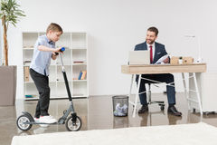 Boy riding skooter while his father businessman working at office Royalty Free Stock Photography