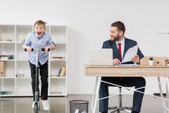 Boy riding skooter while his father businessman working at office Stock Photo