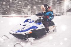 Boy driving snowmobile in a winter landscape. Boy riding snowmobile in a winter landscape Royalty Free Stock Photos