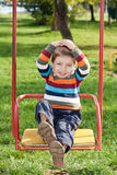Boy riding on a swing Stock Photos