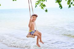 The boy is riding on a swing, on the background of the ocean stock image