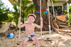 Boy riding on a swing, on the background of a palm tree stock image