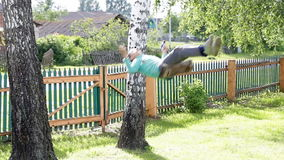 The boy is riding on a swing among the birches. stock footage