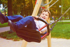 Boy riding on swing in park Stock Images