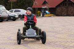 Boy riding a toy car Royalty Free Stock Photos