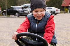Boy riding a toy car Royalty Free Stock Images