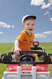 Boy riding toy jeep. A view of a cute toddler riding on an electric toy jeep over an open field on a sunny spring day Stock Photo