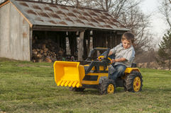 Boy riding tractor Stock Photo