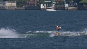 """Wakeboard Man Jump Motorboat. A boy riding wakeboard on wave of motorboat and jumping the wake during the """"Wake Zone Cup"""" on 1 July 2108 in Lake Como stock footage"""