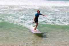 Boy riding wave on purple longboard at the beach. Royalty Free Stock Photo
