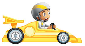 A boy riding in a yellow racing car Stock Image